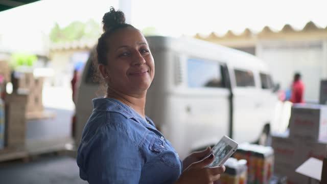 porträt einer lagerarbeiterin mit einem digitalen tablet - weibliche angestellte stock-videos und b-roll-filmmaterial