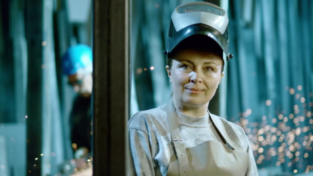 slo mo ds portrait of a female welder - occupazione industriale video stock e b–roll