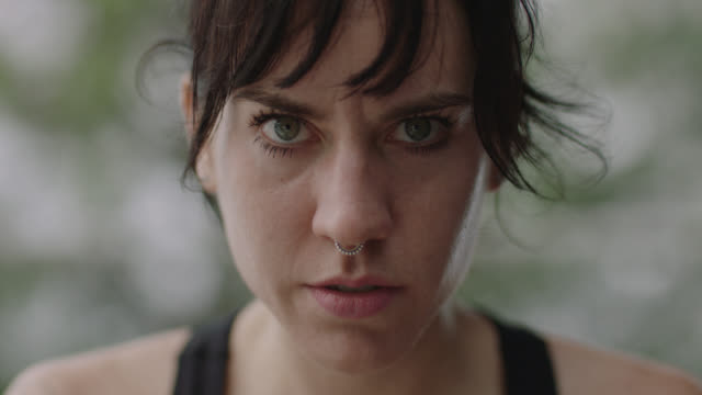 slo mo. portrait of a fierce woman sitting on a set of bleachers and glaring into the camera - determinazione video stock e b–roll