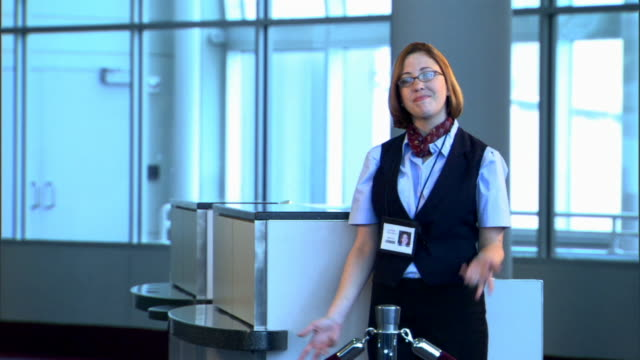 portrait of a flight attendant at the gate shrugging her shoulders. - airline check in attendant stock videos and b-roll footage