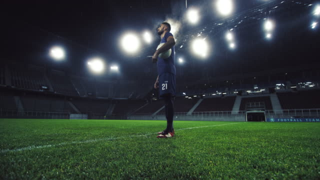 portrait of a football player in an empty stadium at night - ball video stock e b–roll