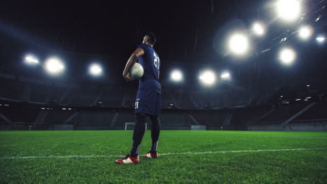 vidéos et rushes de ds portrait of a football player in an empty stadium at night - un seul homme