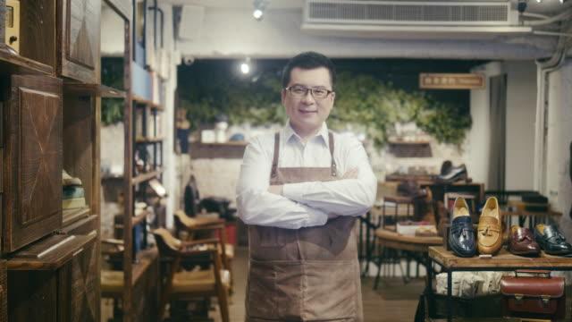vidéos et rushes de verticale d'un propriétaire asiatique amical de magasin de chaussure - gérant