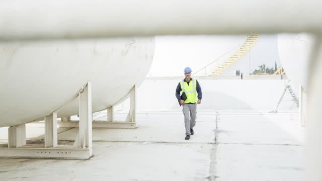TS Portrait of a fuel depot worker as he walks to camera