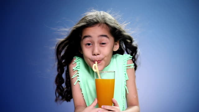 portrait of a girl drinking a glass of juice - saft stock-videos und b-roll-filmmaterial