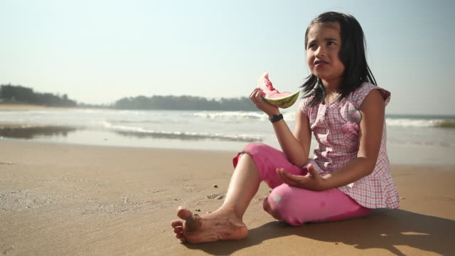Portrait of a girl eating watermelon on the beach