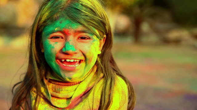 Portrait of a girl playing holi and laughing, Delhi, India