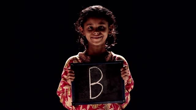 stockvideo's en b-roll-footage met portrait of a girl showing slate - letter b