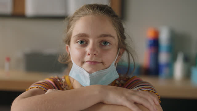 slo mo cu portrait of a girl sitting in a medical clinic and removing her protective face mask - absence stock videos & royalty-free footage