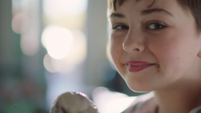 portrait of a girl smiling at the camera in an ice cream parlor eating an ice cream - cibi surgelati video stock e b–roll