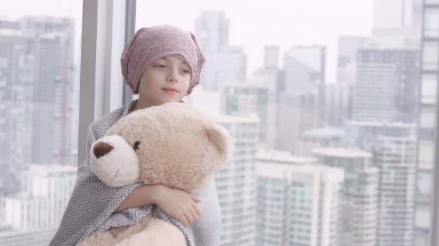 ぬいぐるみを持つ癌の少女の肖像 - 白血病点の映像素材/bロール