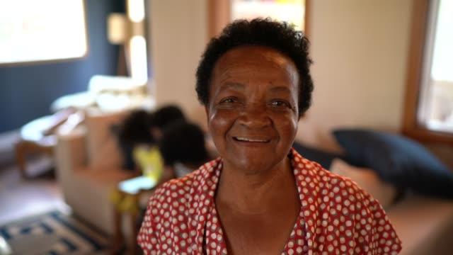 vídeos de stock, filmes e b-roll de retrato de uma avó com sua família que joga no sofá no fundo - avó