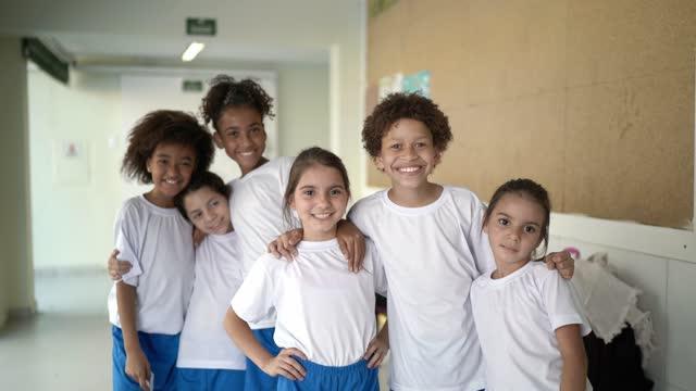 抱き合う小学生のグループの肖像画 - 多様性点の映像素材/bロール