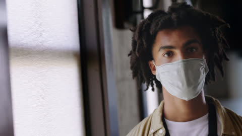 cu portrait of a handsome young man wearing a protective face mask - only young men stock videos & royalty-free footage