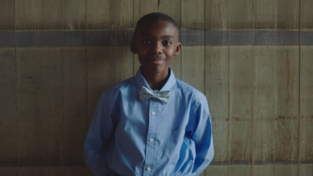 portrait of a happy african-american boy smiling and leaning against a wall - formal stock videos & royalty-free footage