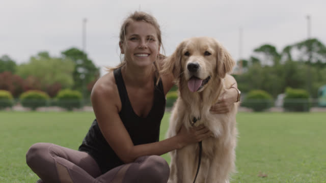 slo mo. portrait of a happy athletic woman sitting in the grass with her arm around her golden retriever - sportkleidung stock-videos und b-roll-filmmaterial