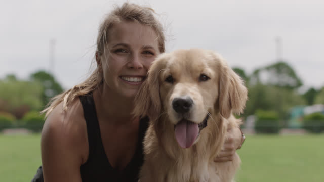 slo mo. portrait of a happy athletic woman sitting in the grass with her arm around her golden retriever - straight hair stock videos & royalty-free footage