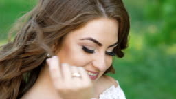 Portrait of a happy bride in wedding dress smiling at camera in a park. Slowly