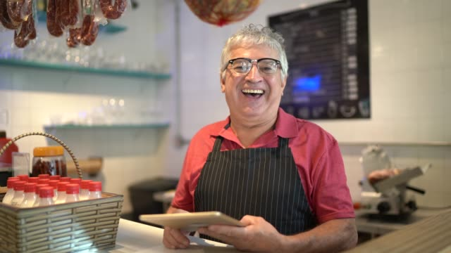 portrait of a happy butcher working using digital tablet - convenience stock videos & royalty-free footage