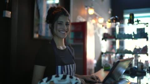 vídeos de stock, filmes e b-roll de retrato de um caixa feliz trabalhando em um bar - loja