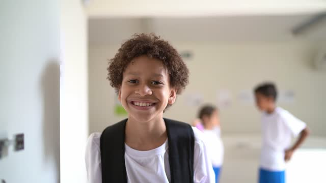 portrait of a happy elementary student in the corridor at school - schoolboy stock videos & royalty-free footage