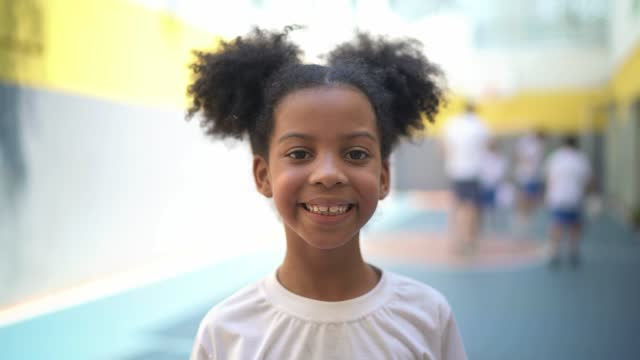 portrait of a happy elementary student in the school's sports court - schoolgirl stock videos & royalty-free footage