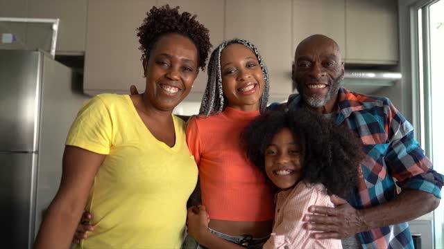 vídeos de stock, filmes e b-roll de retrato de uma família feliz cozinhando juntos em casa - dois genitores