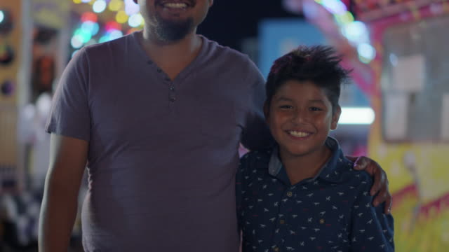 portrait of a happy hispanic father and son at a summer carnival - film moving image bildbanksvideor och videomaterial från bakom kulisserna