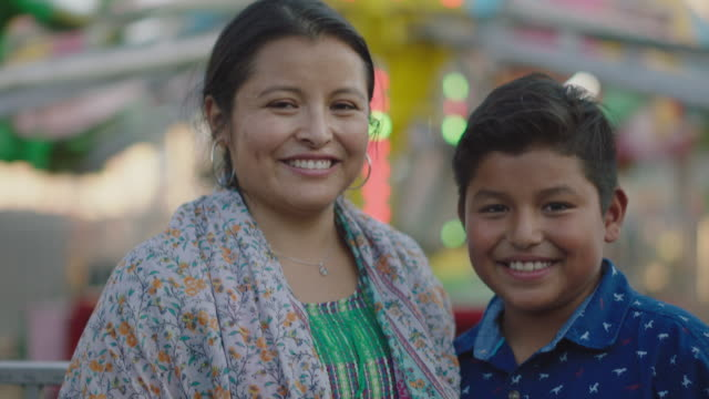 vídeos de stock, filmes e b-roll de portrait of a happy hispanic mother and son at a summer carnival - mulheres de idade mediana