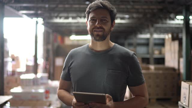 vidéos et rushes de verticale d'un homme adulte moyen heureux dans un entrepôt utilisant une tablette numérique - ouvrier