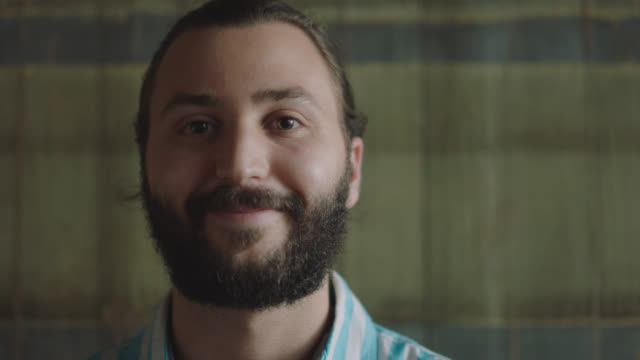 portrait of a happy millennial bearded man smirking into the camera - smirking stock videos and b-roll footage