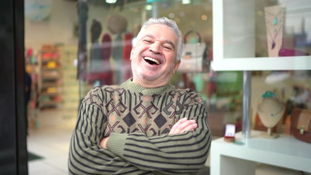 portrait of a happy senior business owner standing with arms crossed in front of a store - pardo brazilian stock videos & royalty-free footage