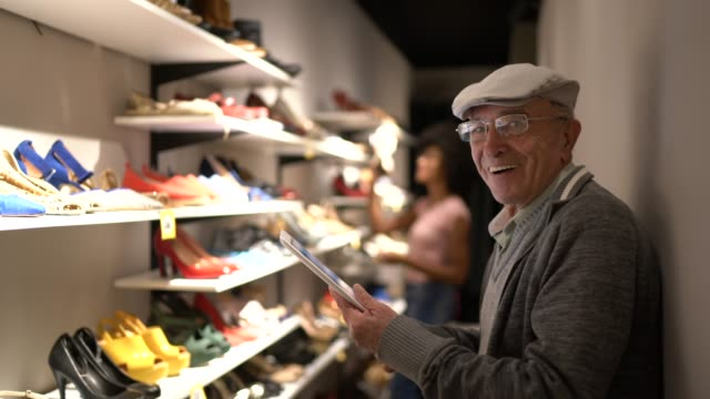 portrait of a happy senior man using digital tablet in a shoe store - e commerce stock videos & royalty-free footage