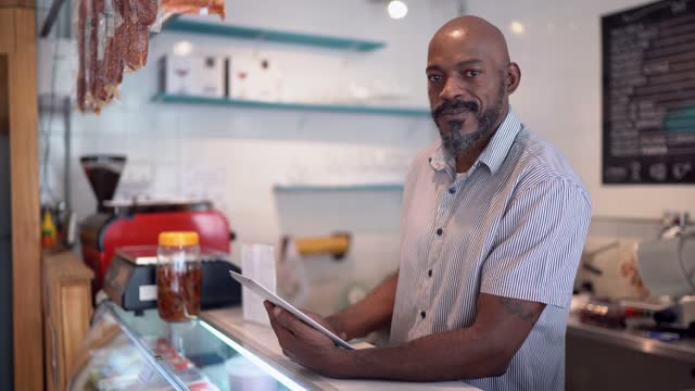 portrait of a happy small business owner using digital tablet - retail occupation stock videos & royalty-free footage