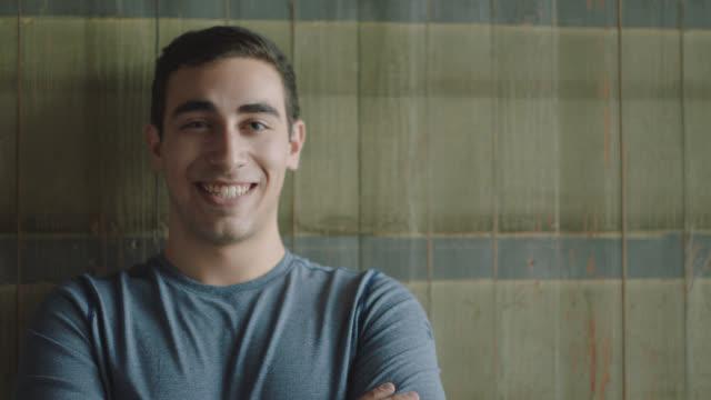 vidéos et rushes de portrait of a happy young man smirking into the camera - musclé