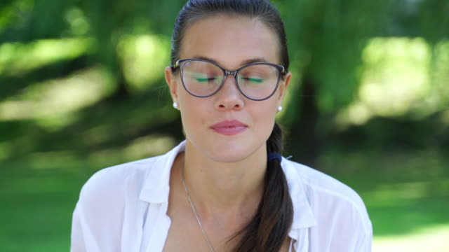 portrait of a happy young woman looking at camera outdoors - coda di cavallo video stock e b–roll