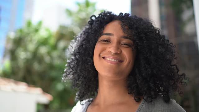 vídeos de stock e filmes b-roll de portrait of a happy young woman outdoors - cabelo natural