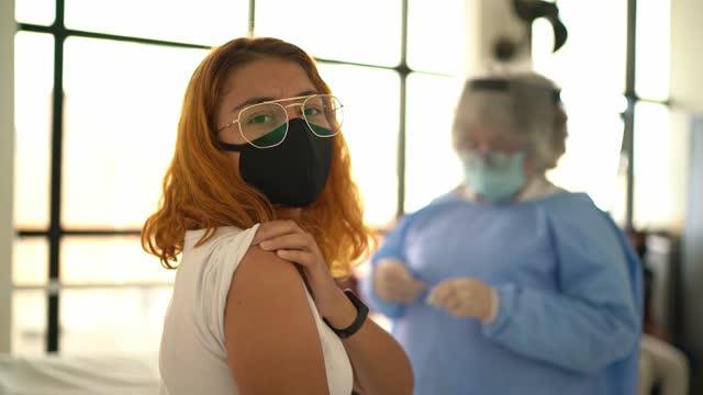 stockvideo's en b-roll-footage met portret van een gelukkige jonge vrouw die vaccin neemt - dat gezichtsmasker draagt - mouw