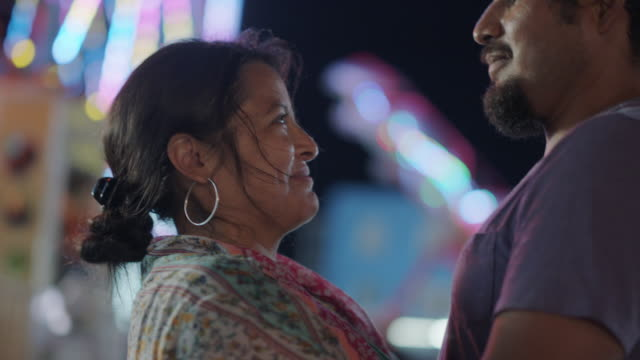 portrait of a hispanic woman embracing her husband at a carnival - latin american and hispanic ethnicity stock videos & royalty-free footage