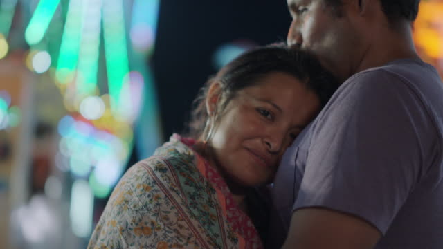 portrait of a hispanic woman resting her head on her husband's chest at a carnival - affectionate stock videos & royalty-free footage