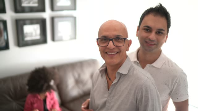 portrait of a homosexual couple at home - daughter on background - gender stereotypes stock videos & royalty-free footage