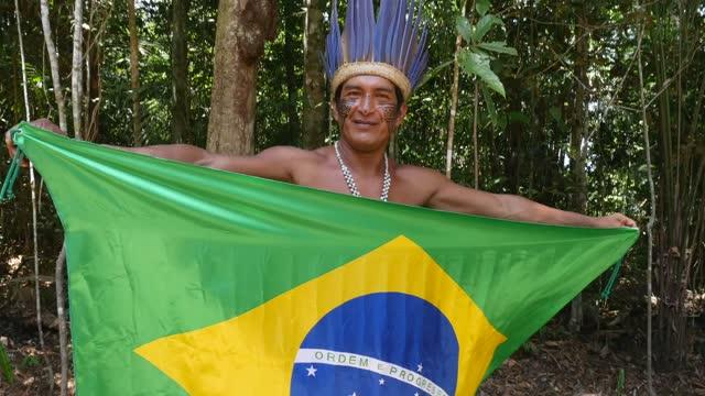 porträt eines indigenen mannes mit brasilianischer flagge - indianischer abstammung stock-videos und b-roll-filmmaterial