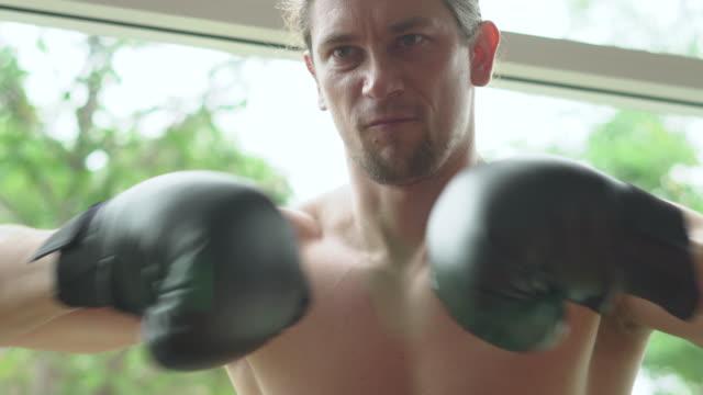 自宅で強烈な男性戦闘機の肖像画 - ボクシンググローブ点の映像素材/bロール