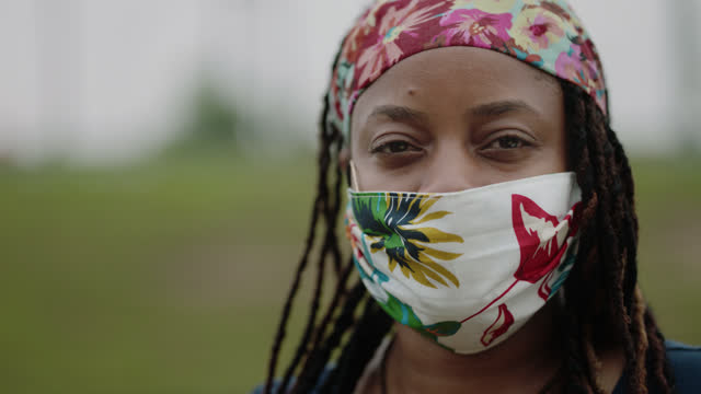 slo mo cu portrait of a intense woman turning to look at the camera while wearing a mask - resilience stock videos & royalty-free footage