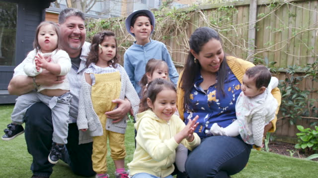 portrait of a large family with children in the back garden - multi ethnic group stock videos & royalty-free footage
