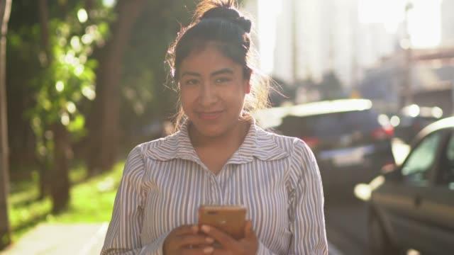 vídeos y material grabado en eventos de stock de retrato de una mujer latina usando celular en la calle - navegar por la red