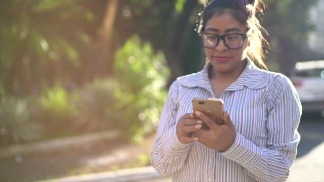 通りで携帯電話を使ったラテン女性の肖像 - ペルー人点の映像素材/bロール