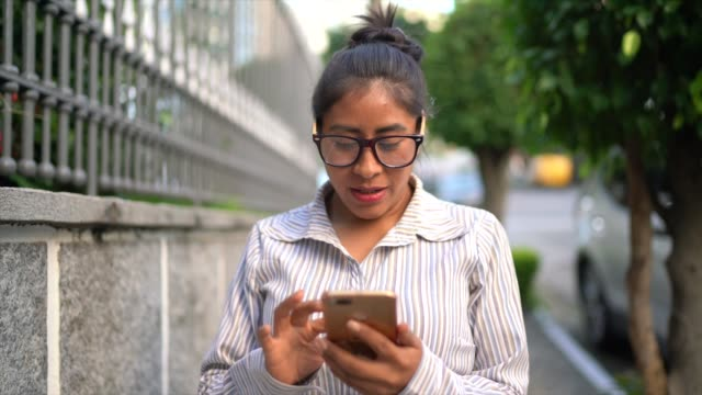 portrait of a latin woman using cellphone in the street - 30 34 years stock videos and b-roll footage