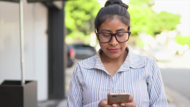 portrait of a latin woman using cellphone in the street - peruvian ethnicity stock videos & royalty-free footage