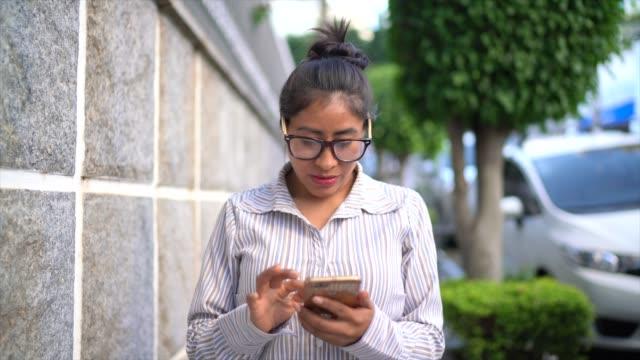 vídeos de stock, filmes e b-roll de retrato de uma mulher latin que usa o telemóvel na rua - óculos
